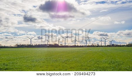 Wind turbines standing on horizon with green grass in foreground and dramatic sky, autumn, Schleswig-Holstein, Germany.