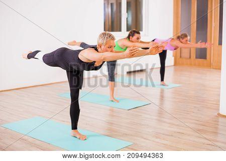 Three girls practicing yoga, Virabhadrasana / Warrior 3 Pose