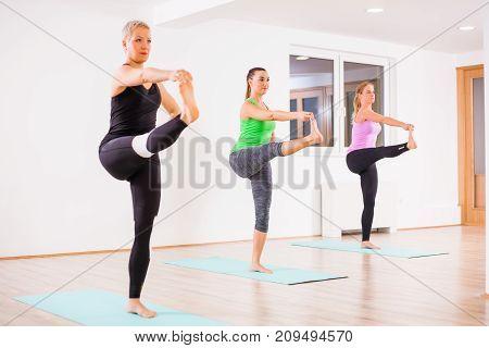 Three girls practicing yoga, Padangusthasana / Hand to big toe pose
