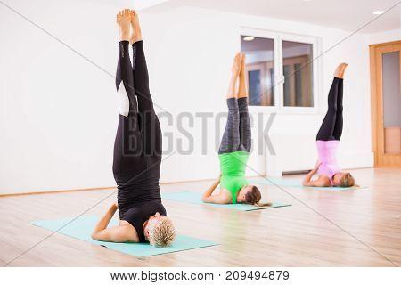Three girls practicing yoga, Salamba Sarvangasana / Supported shoulder stand