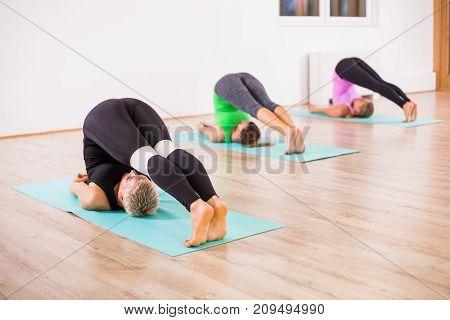 Three girls practicing yoga, Halasana / Plow pose