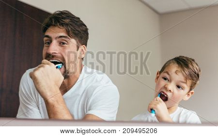 Father and son brushing teeth in bathroom. Young man with his son together brushing teeth and looking in mirror.