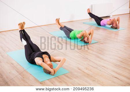Three girls practicing yoga, Matsyasana / Fish pose