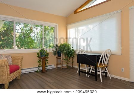 interior of remodeled sunroom addition to home and decor including small table with chairs bamboo flooring and view from window