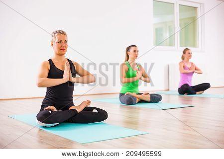 Three girls practicing yoga, Padmasana / Half lotus Position