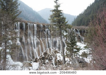Waterfall in the forest. Frozen water drains over the rocks. The rock is covered with moss on which cold water flows.