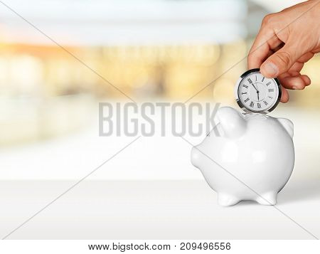Hand clock bank pig piggy time is money background