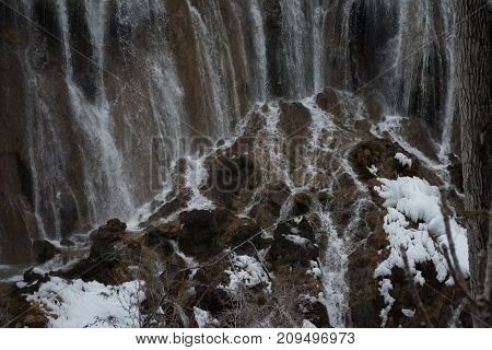 Waterfall in the forest. Frozen water drains over the rocks. The rock is covered with moss on which cold water flows.Waterfall on rocks in a coniferous forest
