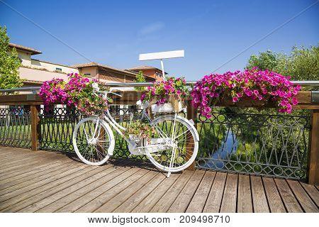 White Bike on wooden bridge with flowers