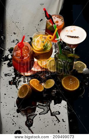 Alcoholic beverage and fruit at restaurant. Drink and food. Cocktails isolated on black background with mojito. Party and summer vacation. Fruit slice and cocktail glass at bar.