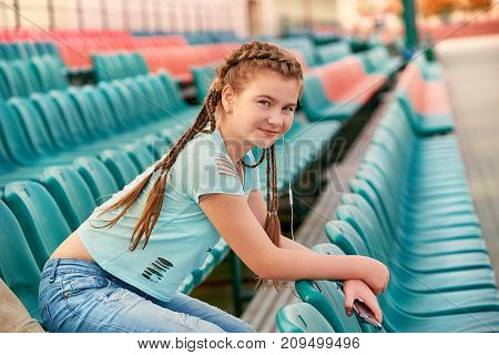 Teenage girl sitting at the stadium in the blue shirt.The stands soft focus blue. Girl loves to listen to the song in the phone