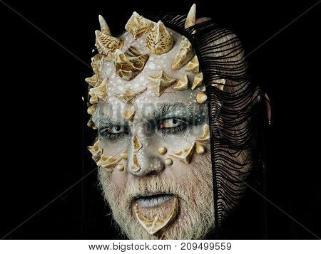 Man with fictional makeup. Demon with scarf on head isolated on black. Monster with white eyes and thorns on face. Alien with dragon skin and grey beard. Horror and fantasy concept.