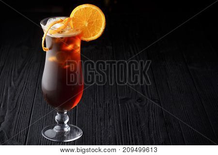 Long Island Ice Tea cocktail on black wooden background