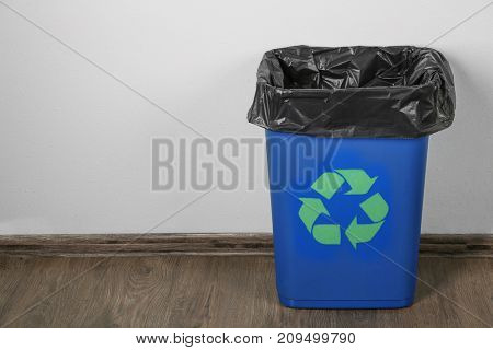 Blue rubbish bin with logo of recycling in room