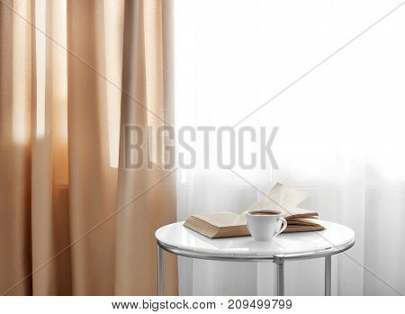 Open book and cup of coffee on table near window with beautiful curtains