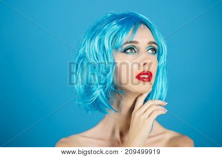 Hairdresser salon and barbershop. Beauty and fashion. Fashion model with naked body and red lips. Woman in blue wig with fashionable makeup. Girl with bright artificial hair copy space