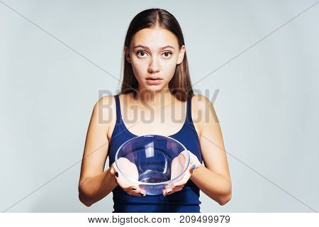 young frustrated girl sits on a diet and looks hungry, shows an empty plate