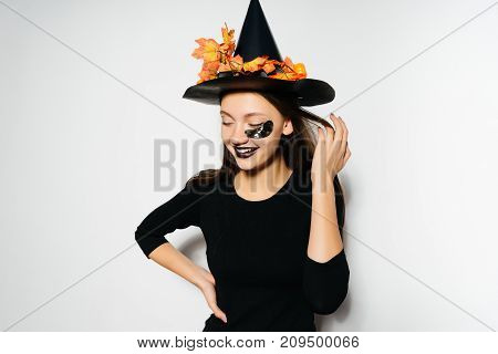Laughing beautiful girl celebrates Halloween in a witch costume and with black lipstick