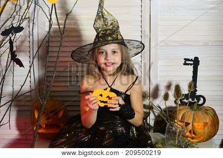 Kid in witch hat and costume holds paper jack o lantern. Little witch with Halloween decor. Girl with happy face on spooky carnival room background. Halloween party and celebration concept