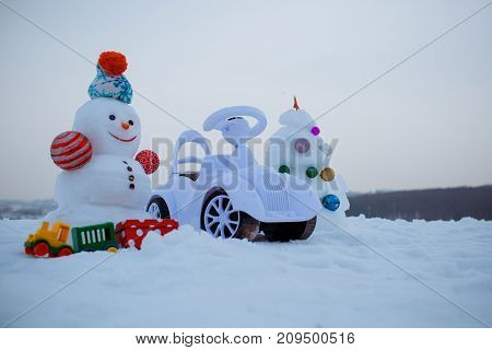 Snowman And Toy Car On Snowy Background