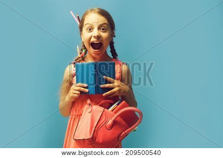 Girl With Pink Bag Holds Open Blue Notebook