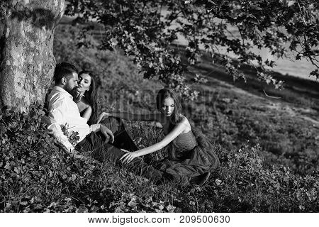 Bearded Man And Two Women On Grass