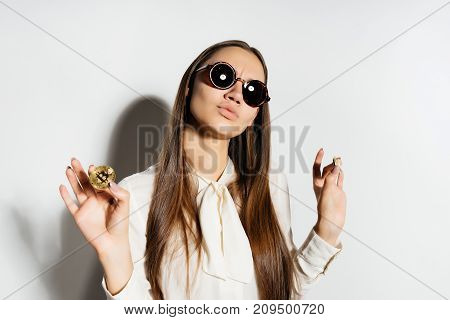 a young modern girl in sunglasses is holding a gold bitcoin, a crypto currency