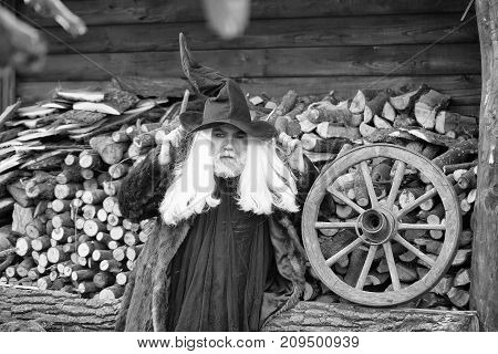 Old man druid with long silver hair and beard in fur coat black Halloween hat on woodpile background