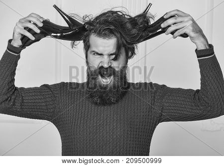 bearded man in red sweater holds fashionable black female shoes as antlers. handsome angry guy with long hair isolated on white background
