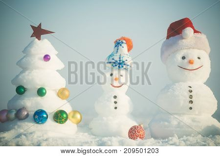 Snow sculptures on blue sky background. Snowmen with smiley faces in hats on winter day. Merry Christmas and happy new year. xmas tree decorated with star and balls. Holidays celebration concept.
