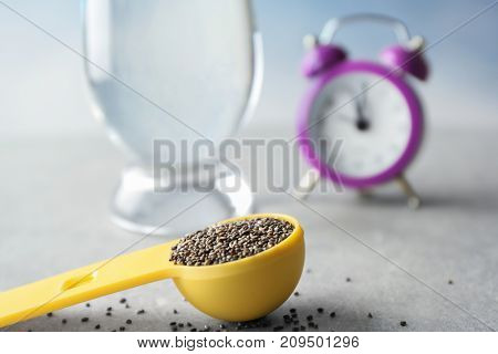 Measuring scoop with chia seeds on table