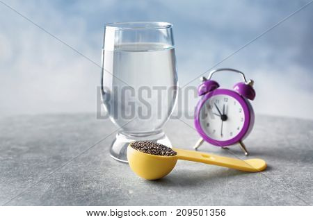 Measuring scoop with chia seeds and glass of water on table