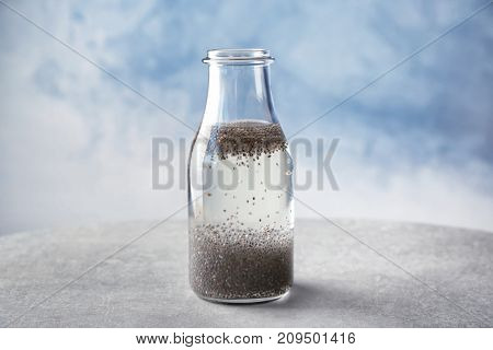 Bottle of water with chia seeds on table