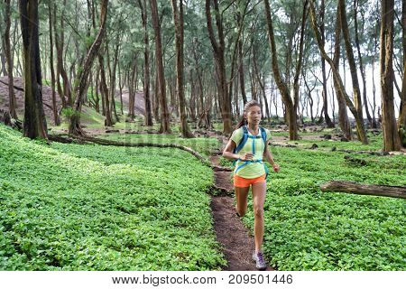 Trail ultra running sport runner athlete woman sprinting in forest green grass. Sport sprinter active doing intense cardio training outdoors in summer landscape.