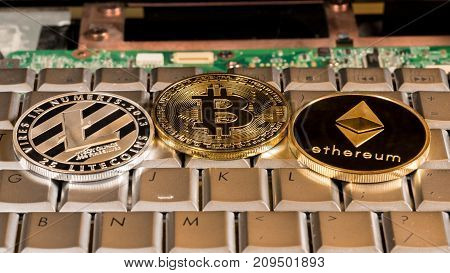 Bitcoin, Litecoin and Ethereum coins on a keyboard to illustrate alternative blockchain and cyber currency