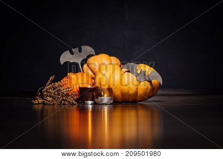 Halloween Carving Pumpkins and gloomy candles lie on a black surface