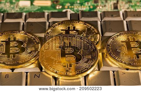 Bitcoin coin on a keyboard with computer board to illustrate blockchain and cyber currency