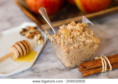 Oatmeal porridge snack with apples cinnamon nuts and honey on marble surface