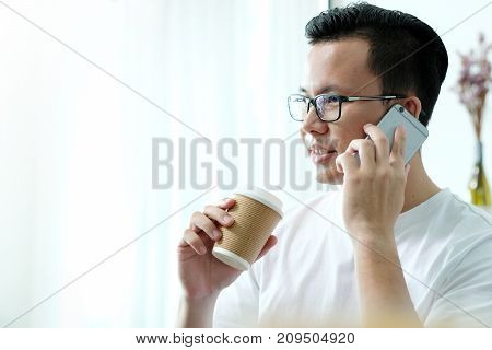 Young asian man talking phone and holding coffee cup in casual lifestyle people on phone