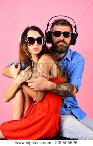 Man with beard hugs pretty girl on pink background. Couple in love wears plastic headphones and sunglasses. Pleasure music and creative lifestyle concept. Music fans with calm faces enjoy music.