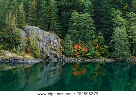 Autumn colors by a peaceful lake with a large rock formation and forest background.