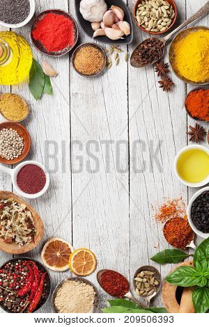 Various spices and herbs on wooden table. Top view with space for your text