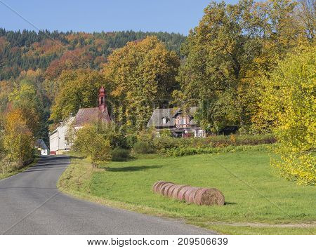 road to the village chapel in autumn rural landscape with straw bales in luzicke hory mountain