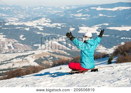 Young woman with snowboard sitting on the slope of hill