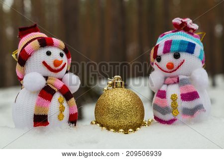 New Year's toys - two snowmen and golden ball on the snow on blurred forest background. Christmas toys