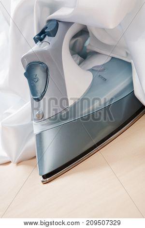 The electric Flatiron under white satin cloth