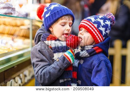Two little kid boys, cute siblings eating sugar apple near sweet stand with gingerbread and nuts. Happy children on Christmas market in Germany. Traditional leisure on xmas.