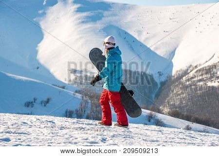Young woman with snowboard walking on the slope of hill