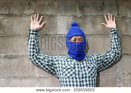 Thief stop and put hands up against brick wall background. Catch burglar concept