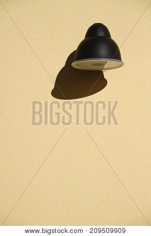 The close up of a wall lamp casting a shadow at a plaster facade.